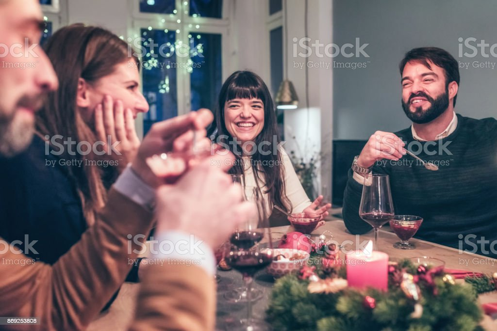 young happy people talking at christmas table stock photo