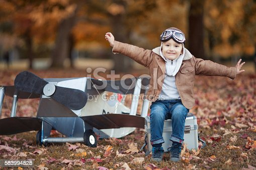 istock Young happy pilot playing aviator 583994828