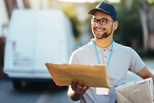 주거 지역에서 배달을 하는 젊은 행복한 우체국 노동자. - postal worker 뉴스 사진 이미지