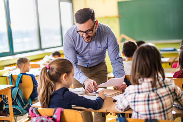 Young happy professor assisting his elementary students on a class at school. stock photo