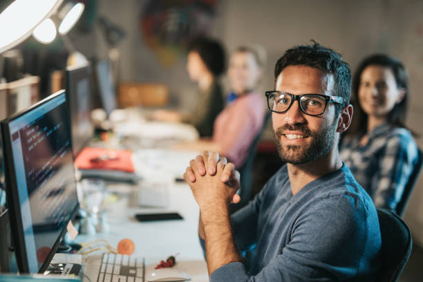 Young happy programmer working on desktop PC in the office stock photo