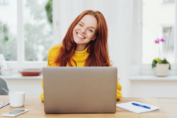 Young happy red-haired woman using laptop Portrait of young happy red-haired woman in yellow sweater using laptop blinking stock pictures, royalty-free photos & images