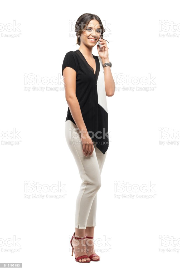 Young happy relaxed business woman talking on the mobile phone smiling and looking at camera. stock photo