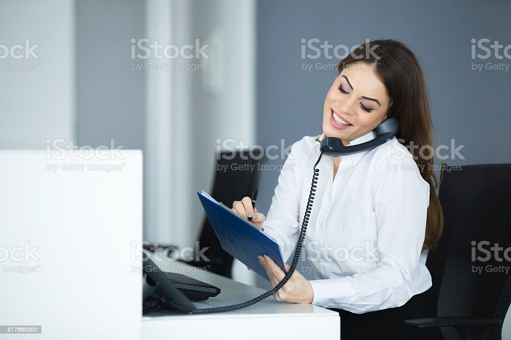 Young happy secretary talking on the phone. stock photo