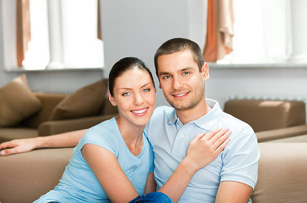 Young happy smiling attractive couple at home stock photo