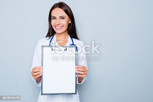 istock Young happy smiling doctor showing folder with diagnosis 947810478