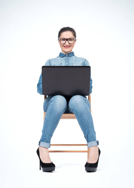 young happy smiling girl in glasses and jeans sits on a chair with a laptop, on light background. front view. - young girl computer home front imagens e fotografias de stock