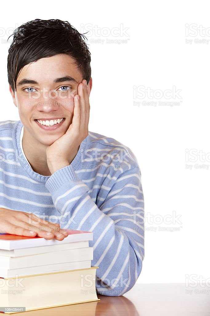 Young happy smiling male student sitting on desk with books royalty-free stock photo