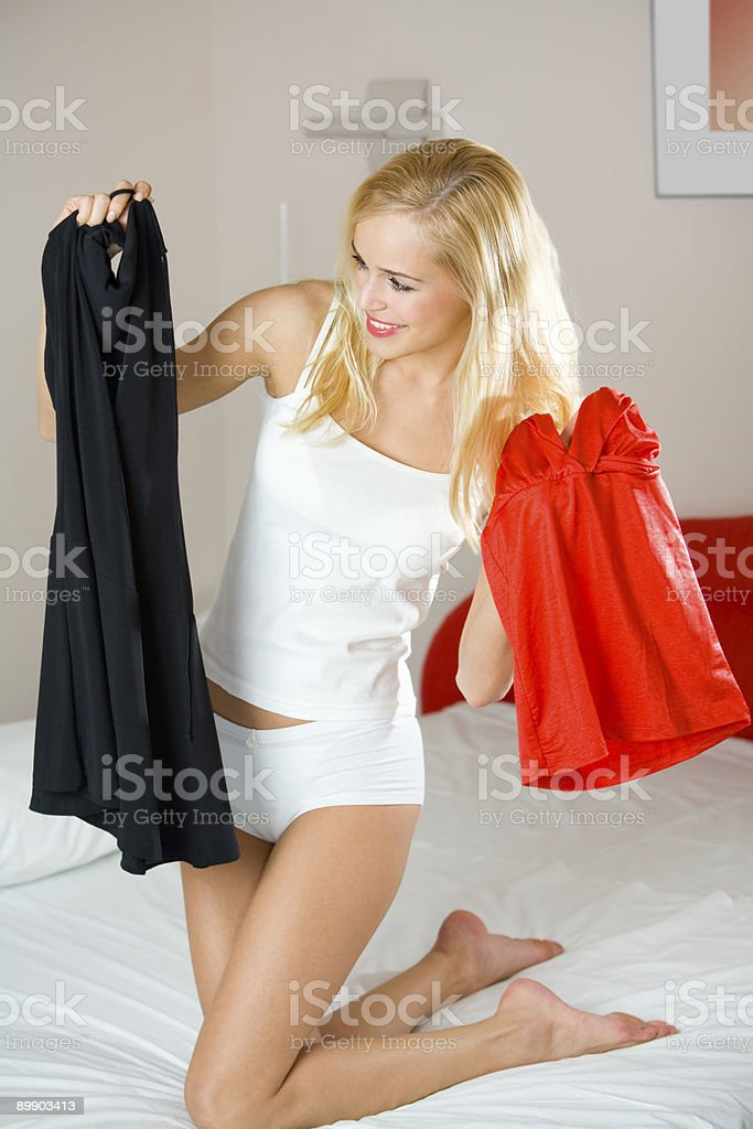 Young happy smiling woman choosing dresses at bedroom royalty-free stock photo