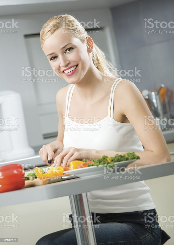 Young happy smiling woman cooking salad at home royalty-free stock photo