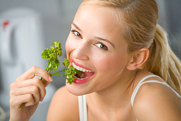 Young happy smiling woman eating at kitchen stock photo