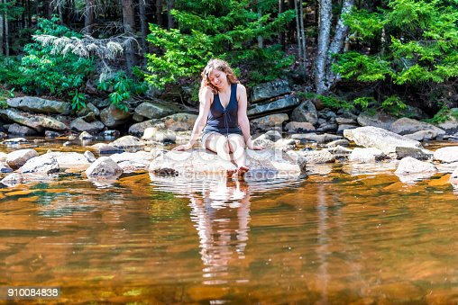 istock Young happy smiling woman enjoying nature on peaceful, calm Red Creek river in Dolly Sods, West Virginia during sunny day with reflection dipping feet in water 910084838