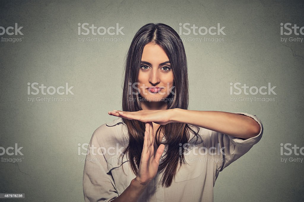 young, happy, smiling woman showing time out gesture stock photo