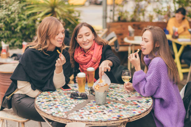 Young happy smiling women eating French fries and drinking beer (and wine) in restaurant - female friendship, having fun and celebration concept.