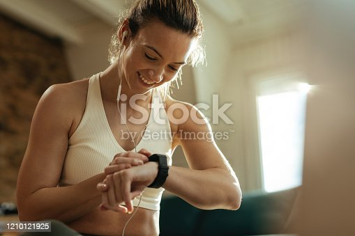 Happy athletic woman measuring heart rate on smart watch while resting after exercising at home.