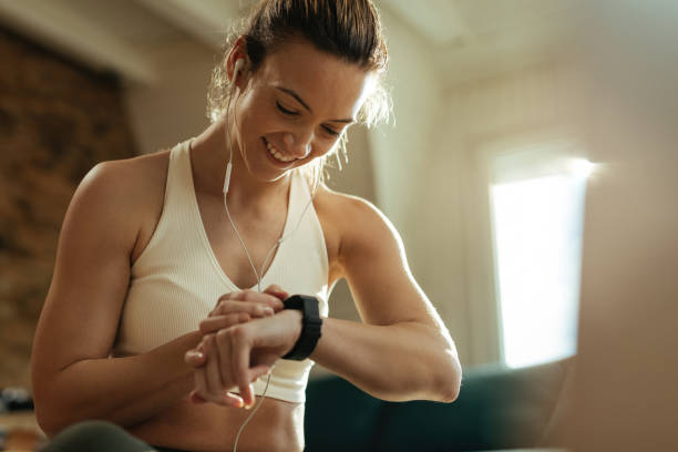 Young happy sportswoman checking heart rate on smart watch after the workout. Happy athletic woman measuring heart rate on smart watch while resting after exercising at home. fitness tracker stock pictures, royalty-free photos & images