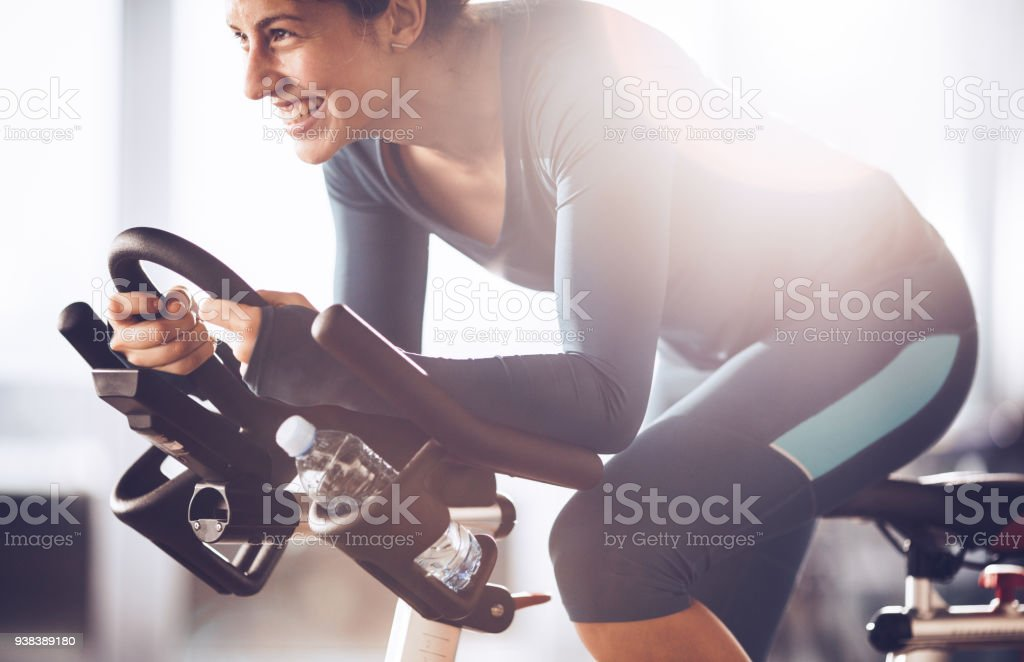 Young happy sportswoman having spinning class on sports training in a health club. stock photo