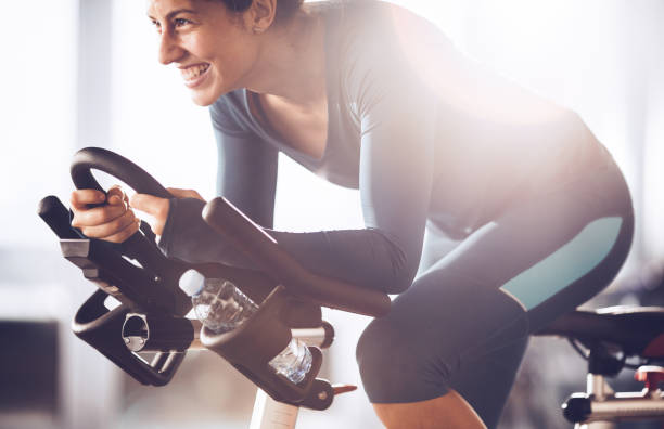 Young happy sportswoman having exercising class on sports training in a health club. Happy athletic woman cycling on exercise bike in a gym. exercise bike stock pictures, royalty-free photos & images