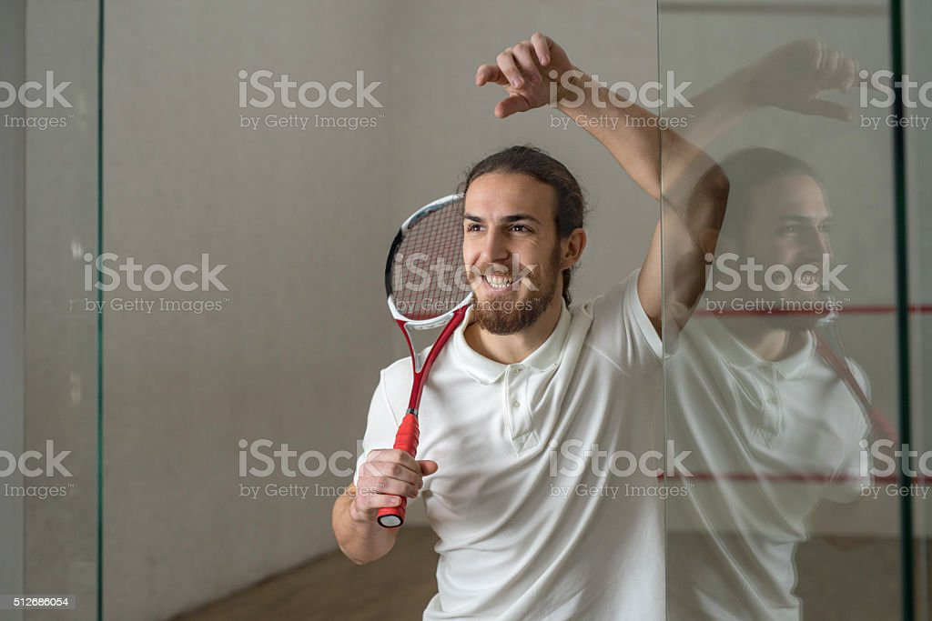 Young happy squash player with a racket. stock photo