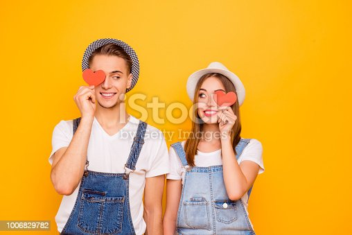 950598260 istock photo Young happy student couple in love wearing hats holding two little red paper hearts on eyes looking foxy at each other, isolated 1006829782