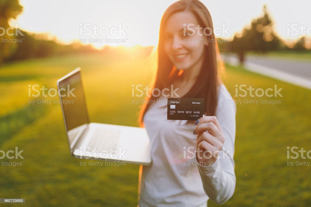 Young happy student female with credit card. Woman sitting on grass...