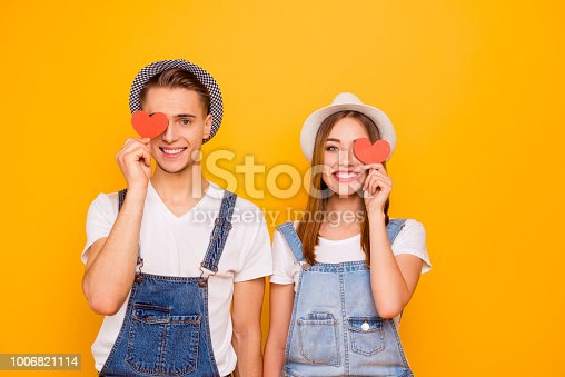 950598260 istock photo Young happy students couple in love wearing hats holding two little red paper hearts on eyes, isolated 1006821114