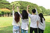istock Young happy students of men and women raising hands celebrating and showing teamwork in the park of school or university. Charity, volunteer and unity concept. 1164705893