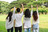 istock Young happy students of men and women raising hands celebrating and showing teamwork in the park of school or university. Charity, volunteer and unity concept. 1166920497