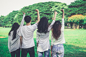 istock Young happy students of men and women raising hands celebrating and showing teamwork in the park of school or university. Charity, volunteer and unity concept. 1168319409