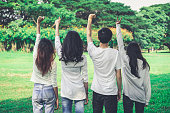 istock Young happy students of men and women raising hands celebrating and showing teamwork in the park of school or university. Charity, volunteer and unity concept. 1173730095