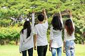 istock Young happy students of men and women raising hands celebrating and showing teamwork in the park of school or university. Charity, volunteer and unity concept. 1176982119