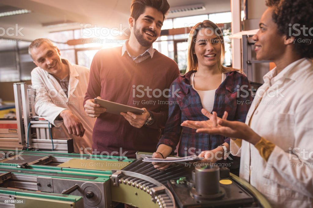 Young happy students talking to engineers in a manufacturing factory. stock photo