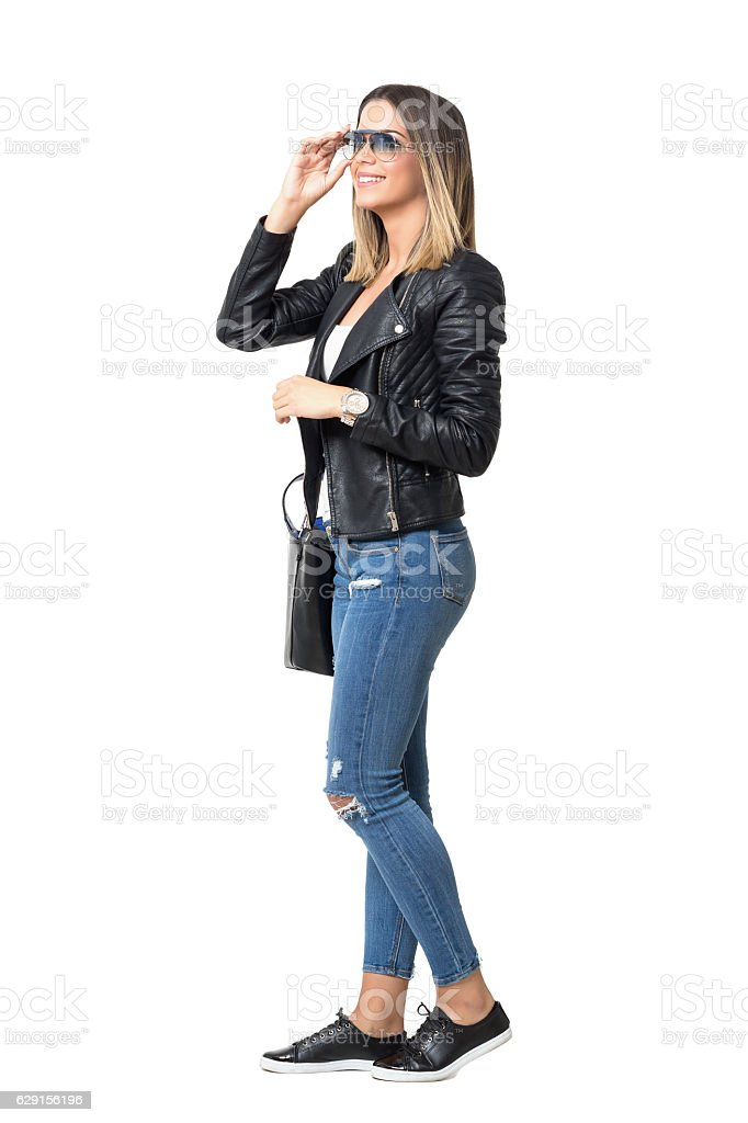Young happy stylish woman in jeans touching sunglasses looking away stock photo