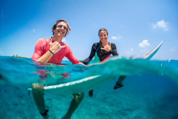 Young happy surfers man and woman sit on the surfboards in the water stock photo