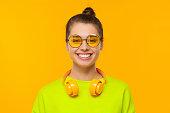 istock Young happy teenage girl wearing neon green sweatshirt, eyeglasses and headphones around neck, smiling and laughing, isolated on yellow background 1247694614