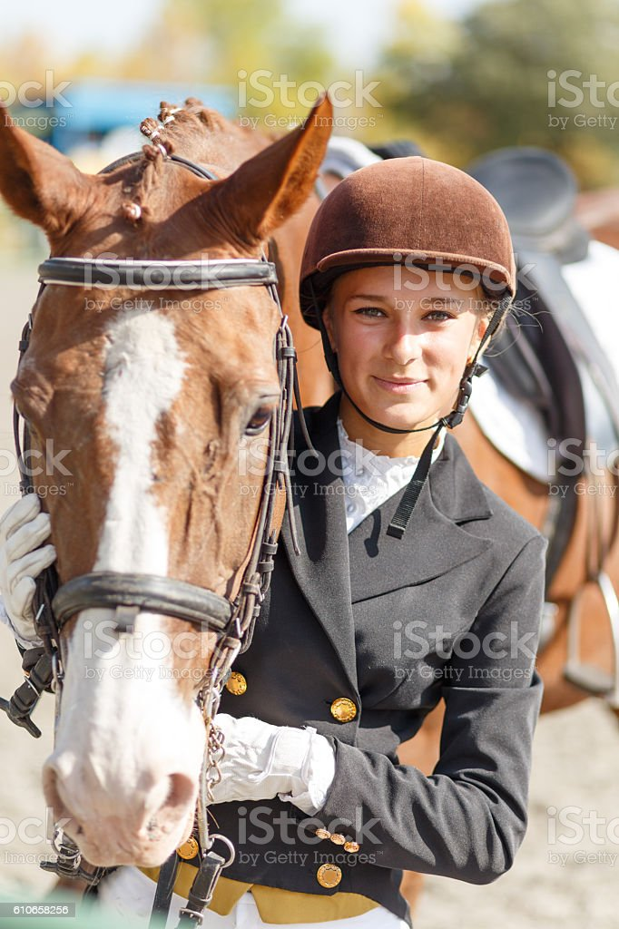 Young happy teenage rider girl with horse stock photo