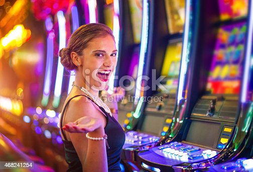 istock Young happy woman at a casino playing with slot machines 468241254