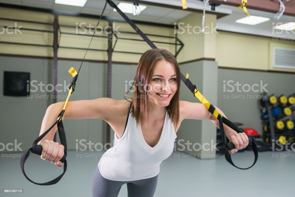 Young happy woman bodybuilder at gym doing elastic rope exercises with with trx fitness straps. stock photo