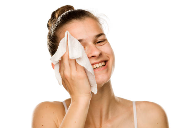 Young happy woman cleaning her face with wet wipe on white background stock photo