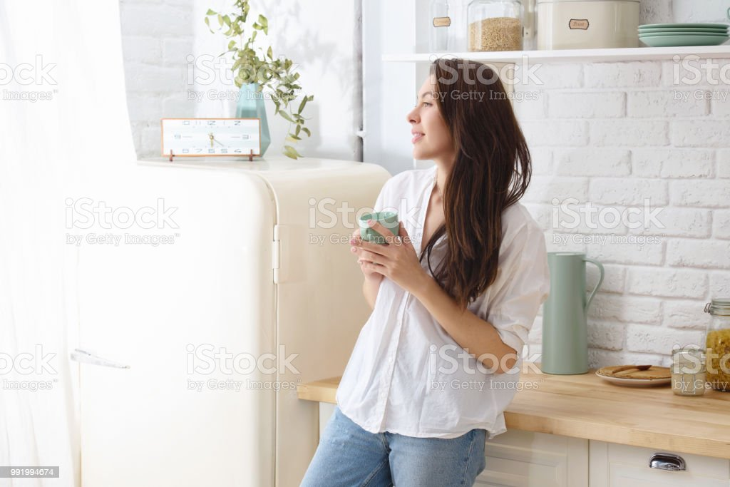 Young happy woman drinking coffee on the kitchen in the morning. royalty-free stock photo
