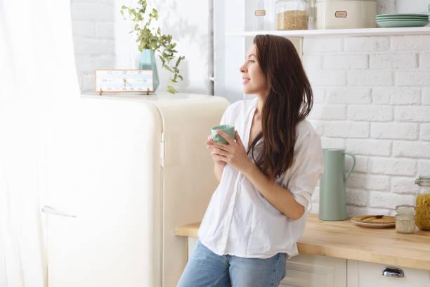 Young happy woman drinking coffee on the kitchen in the morning picture id991994674?b=1&k=6&m=991994674&s=612x612&w=0&h=wzw17dt26q0 avj2le4o86doqzpj9htbv8tvfd5pjuq=