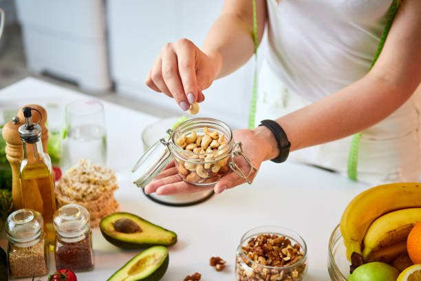 young happy woman eating different nuts (cashew, hazelnut, almond) in modern kitchen. healthy food and dieting concept. loosing weight - frutos secos imagens e fotografias de stock