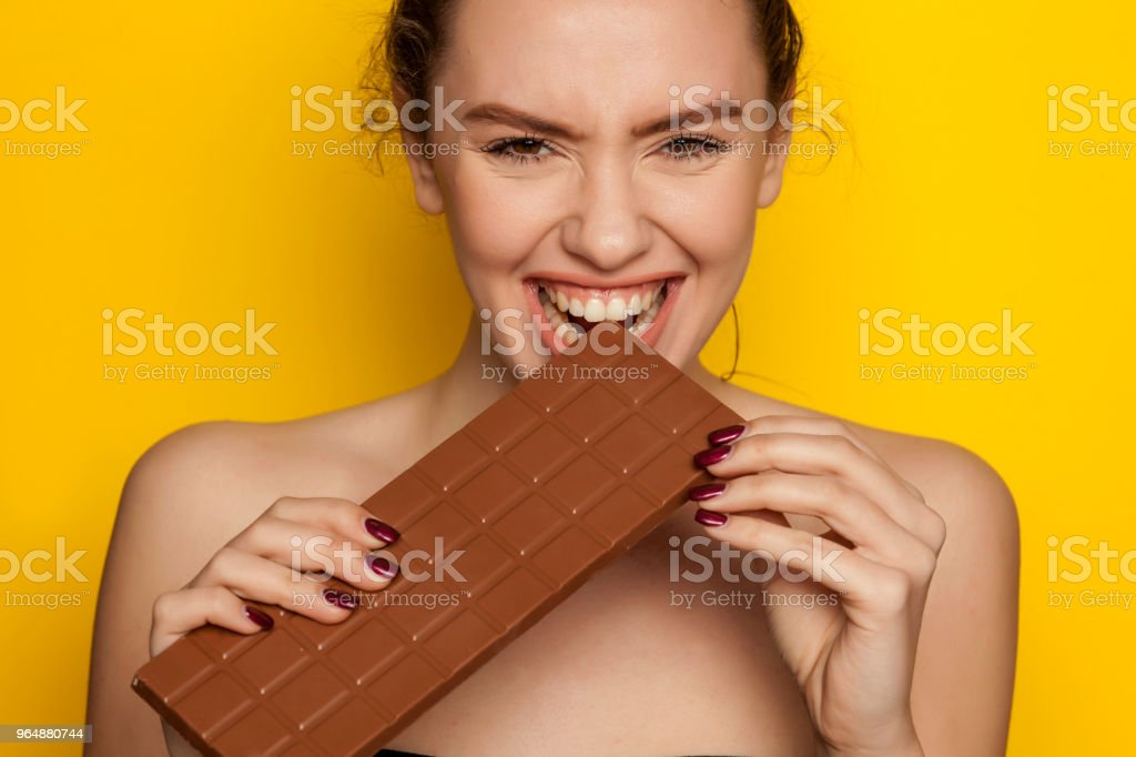Young Happy Woman Enjoying Eating Chocolate On A Yellow Background Stock Photo & More Pictures of Adult