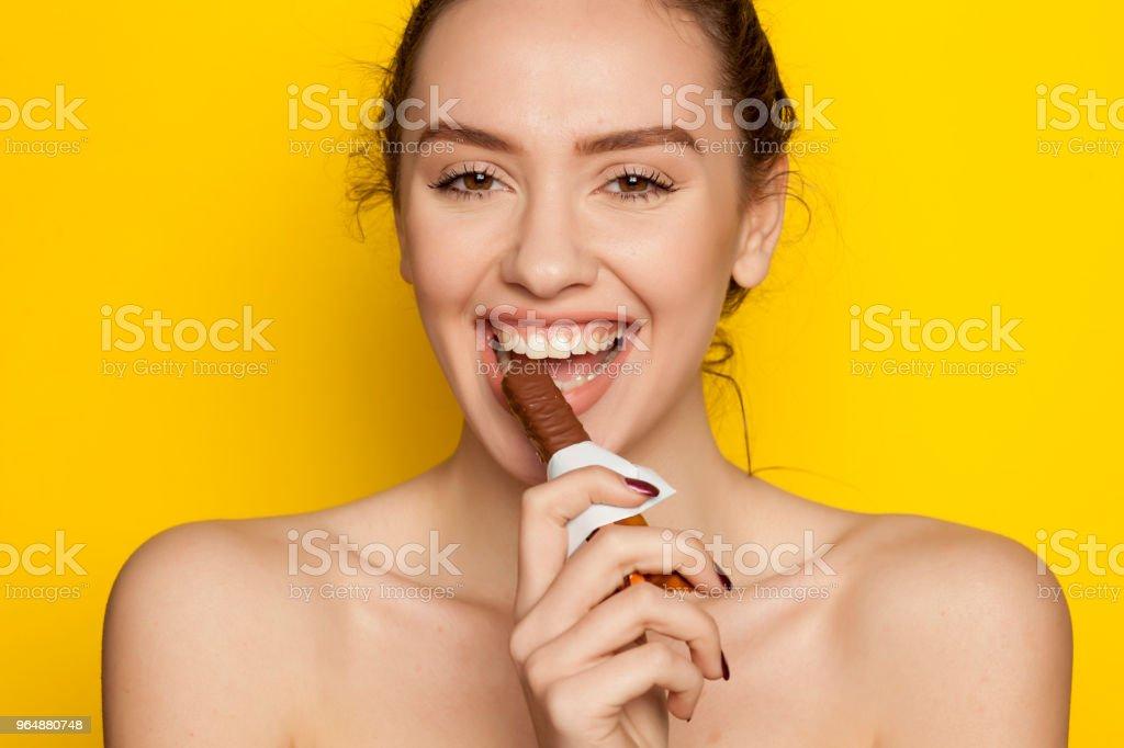 在黃色背景下享受吃巧克力的年輕快樂女人 - 免版稅一個人圖庫照片