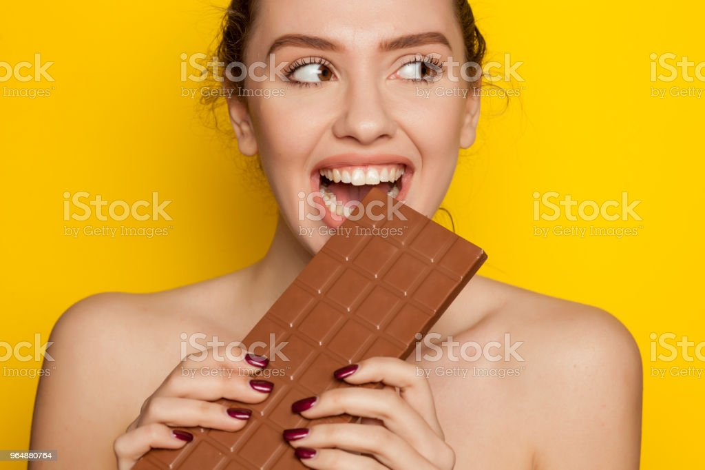 young happy woman enjoying eating chocolate on a yellow background royalty-free stock photo
