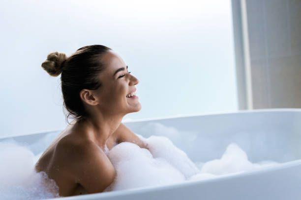 Young happy woman enjoying in bubble bath with her eyes closed. Happy woman enjoying in her bubble bath in a bathroom. bubble bath stock pictures, royalty-free photos & images