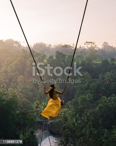 Rear view of a Women sitting on swings at a height of more than twenty meters. In Indonesia Bali Province. Photo of Young tourist woman swinging on the cliff in the jungle rainforest of a tropical Bali island. Young woman swinging in the jungle rainforest of Bali island, Indonesia. Swing in the tropics.
