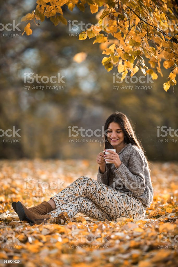 Young happy woman enjoying in hot drink in autumn park. stock photo