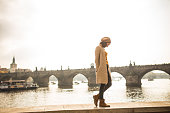 A beautiful young tourist girl standing next to the Vltava river in Prague