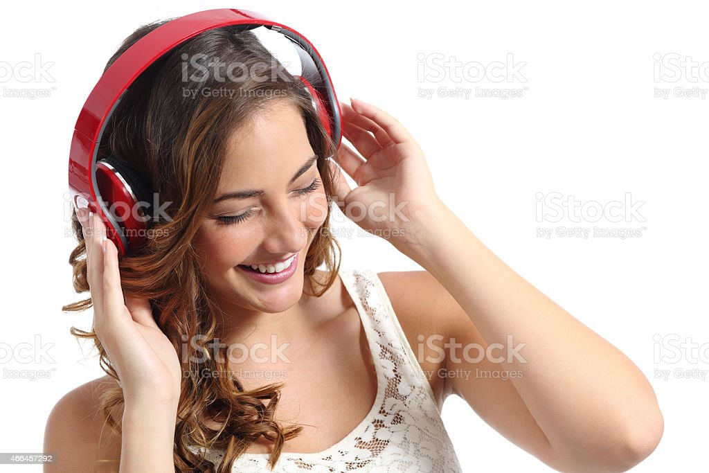 Young happy woman enjoying listening to the music from headphones stock photo